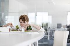 Focused female architect arranging model in conference room Stock Photos