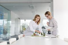 Female architects discussing model in conference room meeting Stock Photos