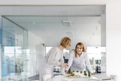 Female architects discussing model in conference room Stock Photos