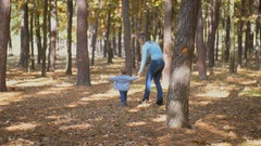 Happy baby boy with mother walking after the squirrel at park Stock Footage