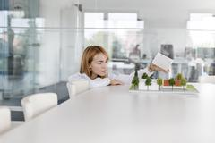 Female architect arranging model in conference room Stock Photos