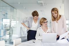Female architects at laptop reviewing blueprints in conference room meeting Stock Photos