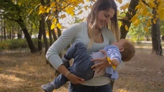 Slow motion footage of happy young mother hugging and spinning her baby son Stock Footage