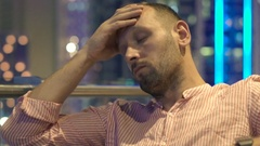 Sad, unhappy man sitting on terrace in cafe at night Stock Footage