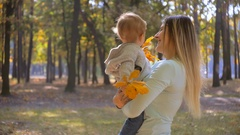 Smiling mother with baby son enjoying walking at autumn park Stock Footage
