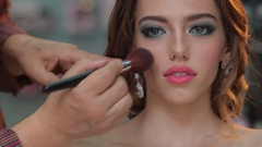 Makeup artist applies powder to the face of attractive girl with make-up Stock Footage