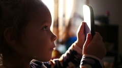 Cute child girl face portrait watch cartoons smart phone against bright window Stock Footage