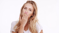 Young beautiful Caucasian blonde girl blowing a kiss picturing imaginary heart Stock Footage