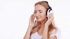 Young beautiful Caucasian blonde girl listening music through headphones dancing Stock Footage