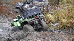 ATV pulled out of the dirty slush near the river with the help of a cable, in Stock Footage
