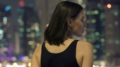 Young woman admire cityscape view on terrace at night Stock Footage