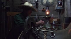 Cowboy Western as seen past old saddle aims shotgun Stock Footage