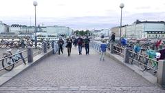 People walk by small pedestrian bridge at Helsinki port, autumn evening Stock Footage