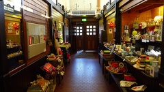 POV walk to wooden exit doors of old market building, pass goods stalls Stock Footage