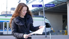 Tourist girl get lost on railway station, hold city map and look around Stock Footage