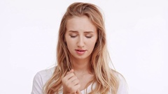 Young beautiful Caucasian blonde girl worried concerned holding hand near mouth Stock Footage