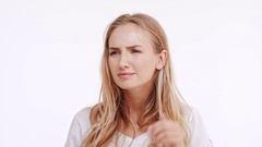 Young beautiful Caucasian blonde girl trying to hear something showing ear on Stock Footage