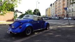 Cabriolet car with canvas top parked at old city street, rear side view Stock Footage