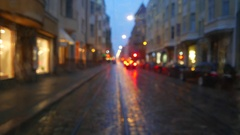 Rear plate blurred view, evening city street after rain, defocused look Stock Footage