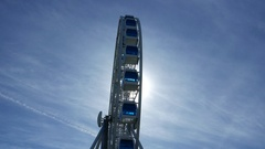 White Ferris Wheel spin against blue sky and sun, light flash through cabins Stock Footage