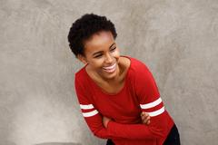 Attractive young modern black woman laughing with arms crossed Stock Photos