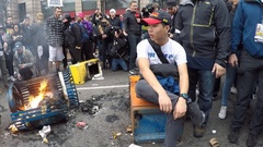 A dejected Trump supporter sits in the middle of an anti-Trump riot Stock Footage