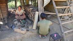 Man sharpen knife in Laos village Stock Footage