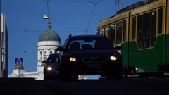 Cars and tram pass along street, flat perspective against Helsinki Cathedral Stock Footage