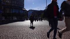 Citizens come across sett paved city street, high contrast shot Stock Footage
