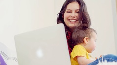 Happy young family sitting on the sofa using laptop together at home in living Stock Footage