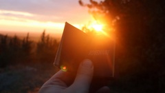 Adventure concept. Book with the inscription and sunset Stock Footage