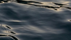 Llight reflecting in the dark and undulating waves of the sea Stock Footage