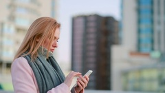 Girl in a pink coat with phone walks on a modern city. background of skyscrapers Stock Footage
