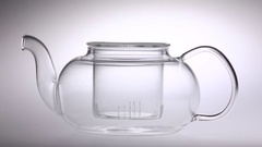 Two tablespoons of tea poured in transparent teapot. White background Stock Footage