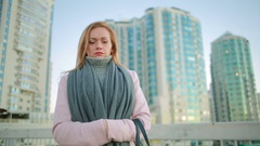 Girl in a pink coat walks on a modern city on the background of skyscrapers Stock Footage