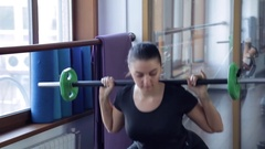 In the gym young brunette kneels and holds bodibar on his shoulders Stock Footage