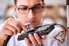 Proffesional repairman repairing broken hard drive Stock Photos
