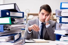 Busy businessman under stress due to excessive work Stock Photos