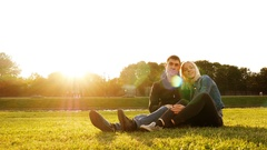 Love couple sitting on grass in summer park Stock Footage