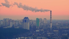 Aerial view  of smoking chimneys in a residential area of the city at sunset Stock Footage