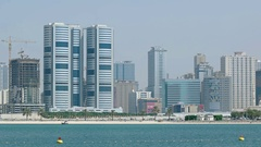 Highrise Buildings tower over Desert Highway and Bay Stock Footage