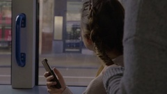Young Woman Holds Smartphone, While Her Friend Braids Hair, On The Light Rail Stock Footage