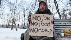4K.Homeless young man with cardboard in  winter city park close up Stock Footage