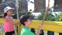 Kids knock on Thai shrine bells At Wat Khao Takiap Stock Footage
