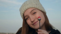Pretty teenage girl in gray knitted hat eating lollipop in front of camera and Stock Footage