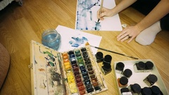 The girl draws a palette of watercolor paints.Creating a watercolor painting. Stock Footage