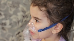 Beautiful curly girl making inhalation close up. Treats cough Stock Footage