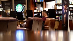 Pan shot of people drinking coffee and reading book inside Starbucks store Stock Footage