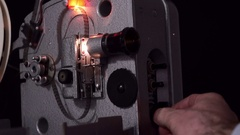 Retro movie projector on a black background. The film 8 millimeters. Stock Footage
