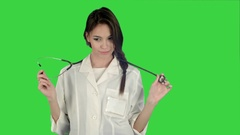 Funny female doctor playing with a stethoscope on a Green Screen, Chroma Key Stock Footage